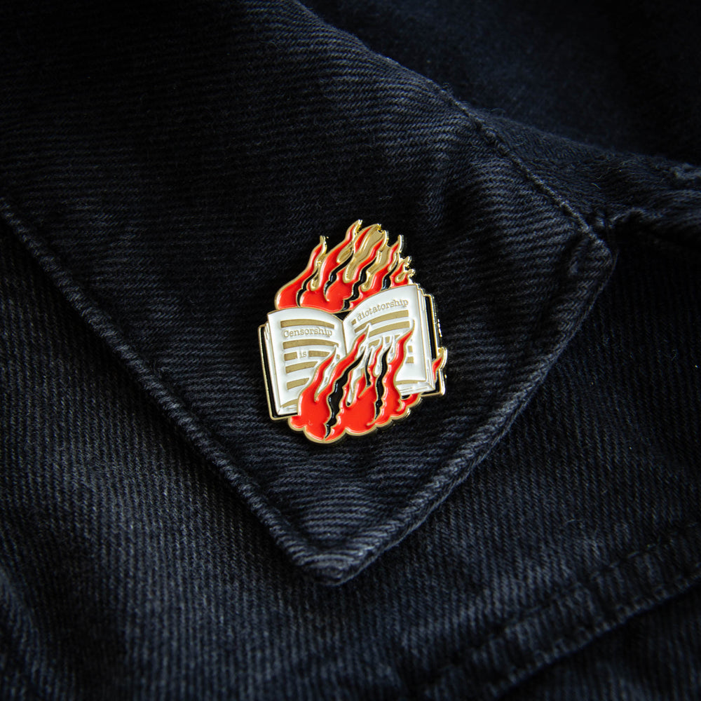 A gold enamel pin of a book in flames on the lapel of a black denim jacket for unisex adults.