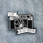 "A cool enamel pin of a broken camera with banners and the quote, ""Live in the Moment""."