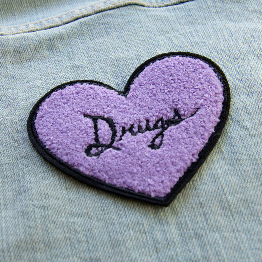 "A spooky, fuzzy patch for women of a purple heart with the word, ""Drugs"" on it."