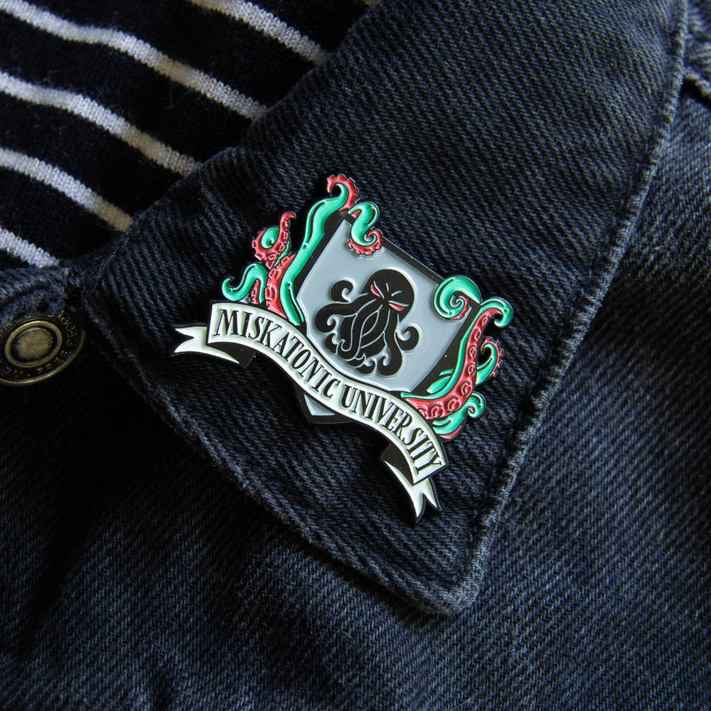 A cool lapel pin of the Miskatonic University crest, featuring Cthulhu.