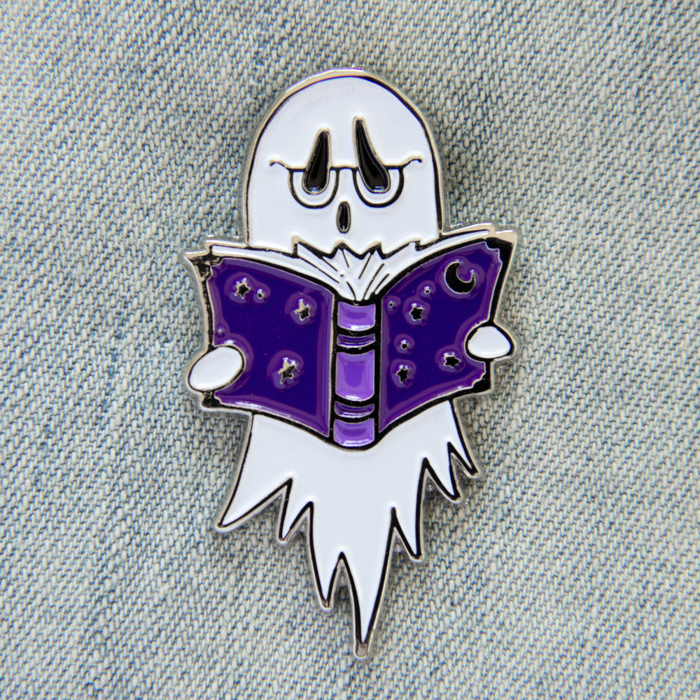 A cute enamel pin of a ghost wearing glasses and reading a purple book with stars on it.