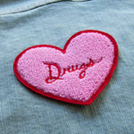 "A creepy cute patch of a chenille heart with the word, ""drugs""."