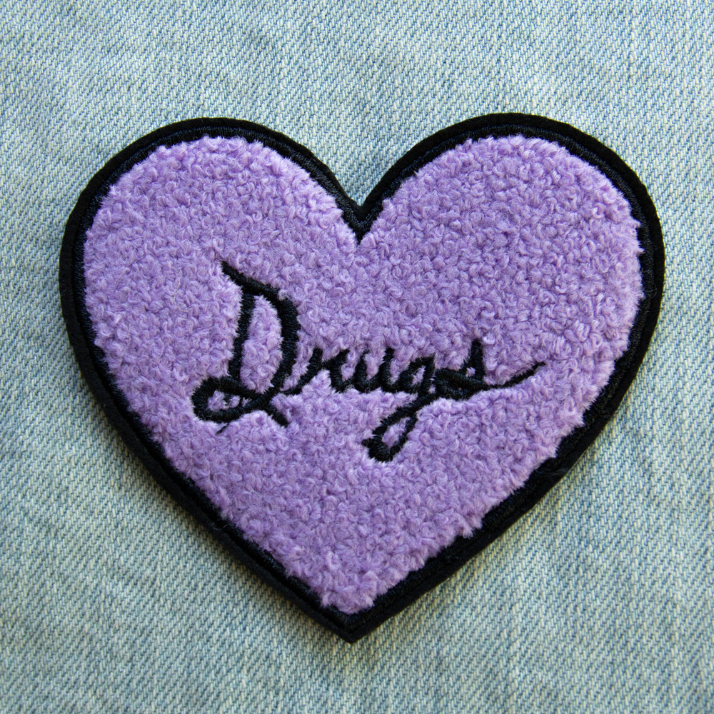 "A cool iron on patch of a fuzzy chenille heart in purple with the quote, ""Drugs"" in black embroidery."