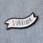 "A black and white unisex enamel pin of a banner with the word, ""Survivor""."