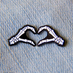 Two enamel pins of skeleton hands making a heart symbol.