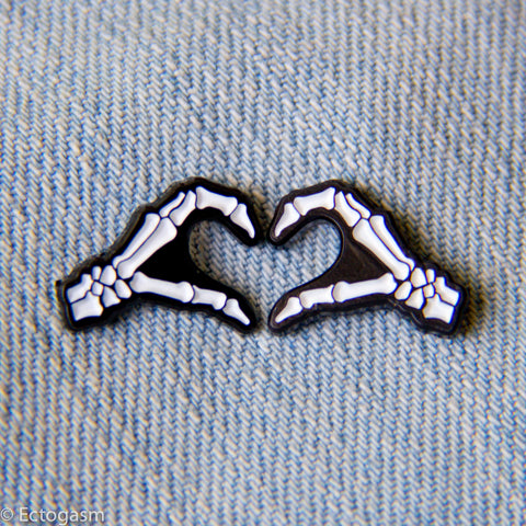 A pin set of skeleton hands forming a heart.