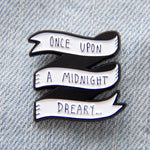 "A black and white enamel pin with the quote, ""Once Upon A Midnight Dreary..."""