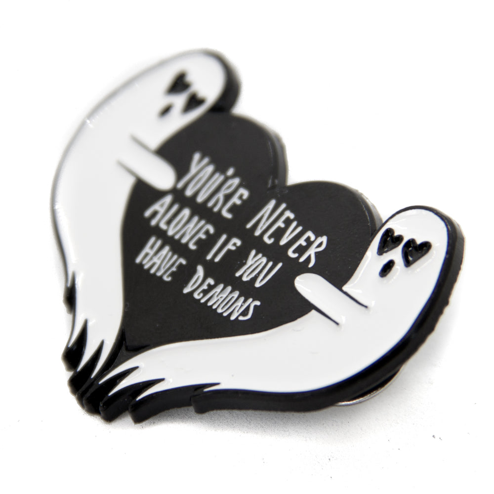 A black and white metal and enamel pin of two ghosts with a funny quote.