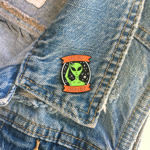 A cool alien and space ship pin on the lapel of a denim vest for grunge style.