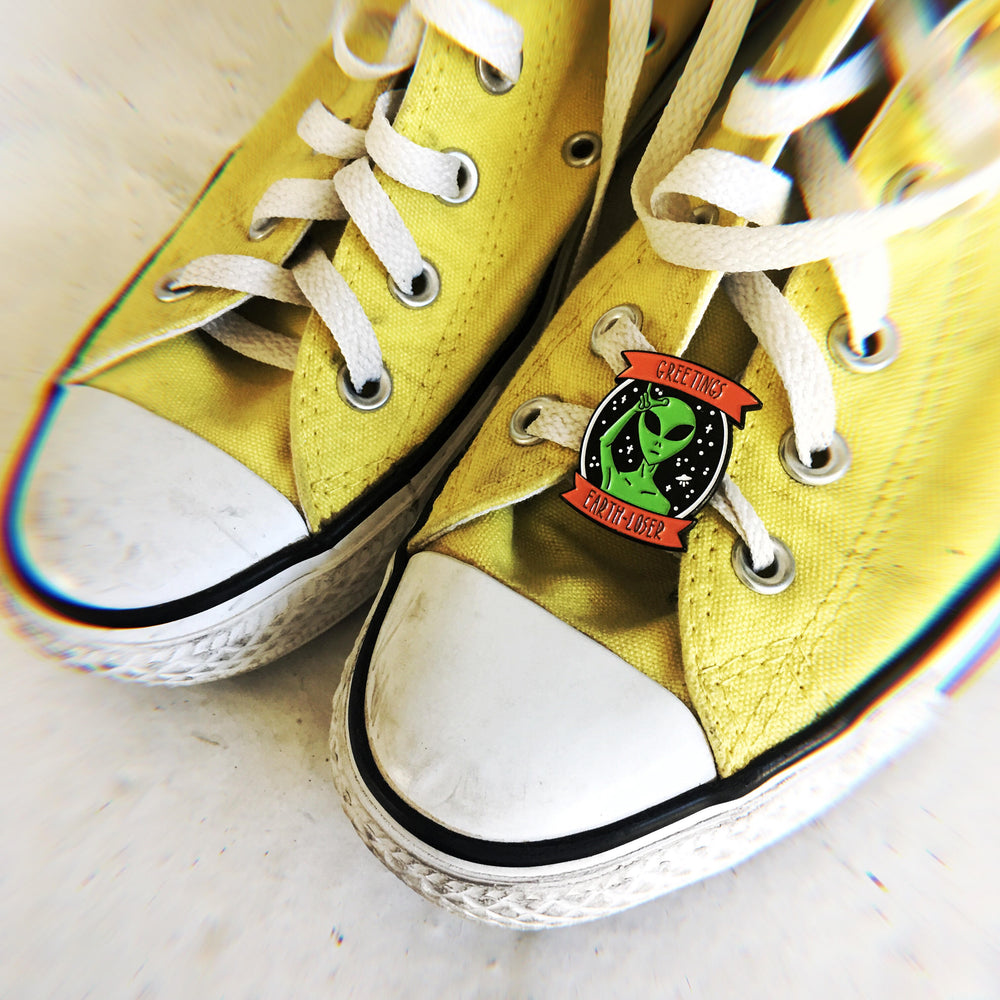 A funny green alien enamel pin on a pair of yellow converse for teen grunge fashion.