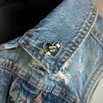"An enamel pin of a black and silver heart with a knife and the quote, ""horror movies"", pinned to the lapel of a denim jacket for spooky style."
