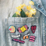 A colorful enamel pin collection on a jacket pocket for art hoe fashion.