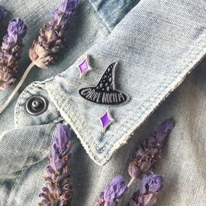 A black witch hat pin on the lapel of a denim jacket surrounded by lavender flowers.