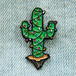 A holiday enamel pin of a saguaro cactus wrapped in string lights like a Christmas tree.