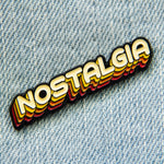 "An enamel pin of the word, ""nostalgia"" in warm 70's themed colors."