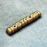 "A cool vintage enamel pin of the word, ""nostalgia"" on a denim jacket."