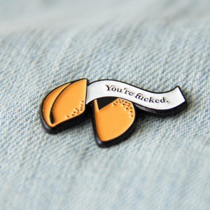 A cool enamel pin of a fortune cookie with a curse word quote. Shown on a denim vest for alternative fashion.