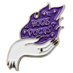 "An enamel pin of a hand holding a purple flame with the quote, ""Hocus Pocus""."