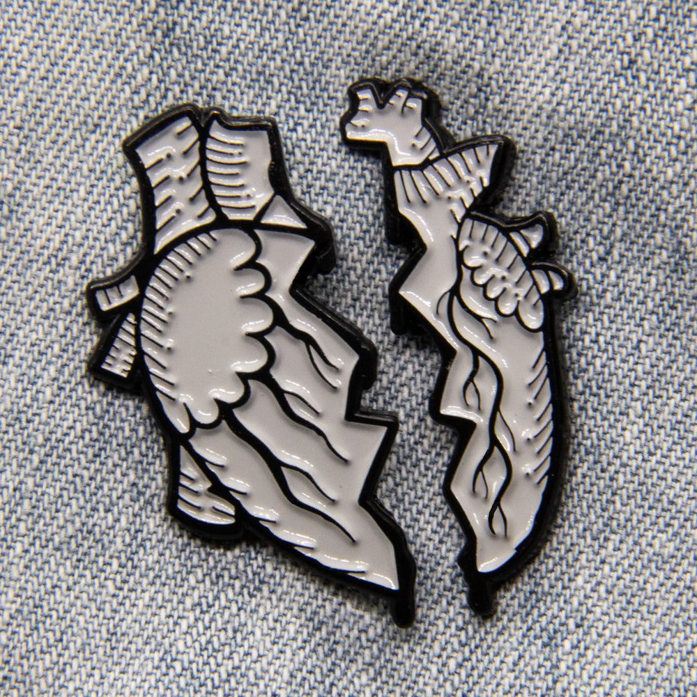 An enamel pin of two halves of a broken anatomical heart, in black and grey. Pictured on a denim jacket for goth style.