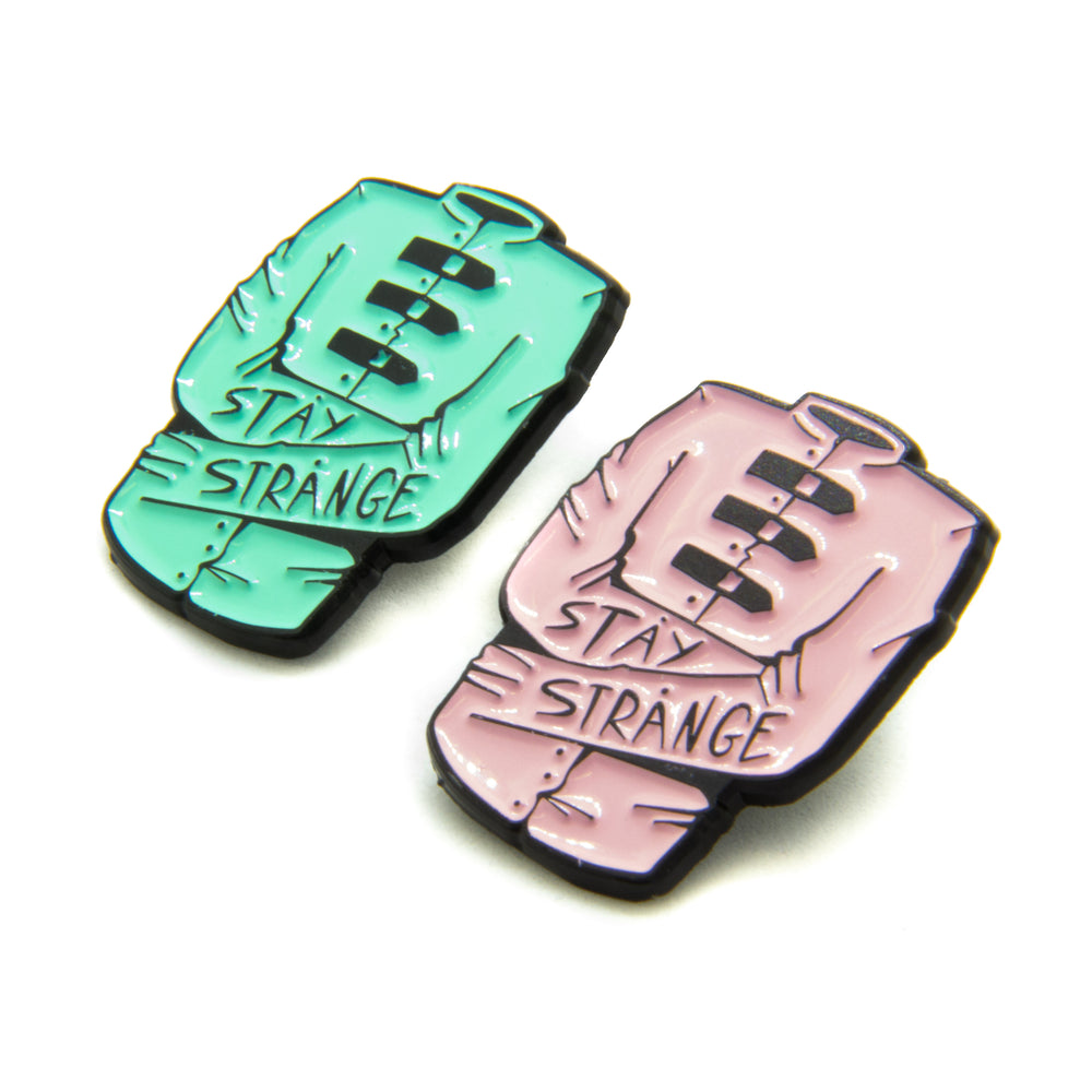 "Two straight jacket enamel pins with the quote, ""stay strange"". Available in Ectogasm green or pastel pink."