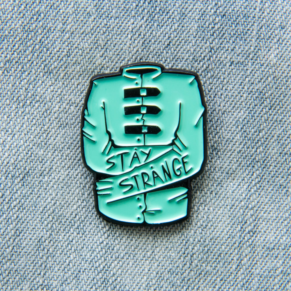 "An Ectogasm green enamel pin of a straight jacket with the phrase, ""Stay Strange"" written across the sleeves in spooky, goth letters."