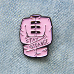 "A pastel goth enamel pin of a pink straight jacket with the quote, ""Stay Strange"" on the sleeves. Makes a cute gift for couples."