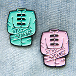 """Stay Strange"" quote enamel pins of pastel colored straight jackets. Designed by Ectogasm."