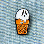 A funny enamel pin of a white and orange ice cream cone with a ghost's spooky face, pictured on a denim vest. Great for punk style.