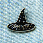 "A black and silver lapel pin of the quote, ""Carpe Noctem"" for spooky goth fashion. Designed by artist Ectogasm."