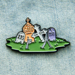 "A dark humor enamel pin of a graveyard with the quote, ""It's All Good in the Hood""."