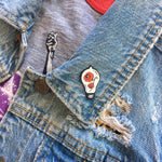 A cool traditional tattoo art pin on the lapel of a denim vest for women's edgy fashion.