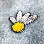 A side view of a yellow and white flower enamel pin on a denim jacket for spring fashion.