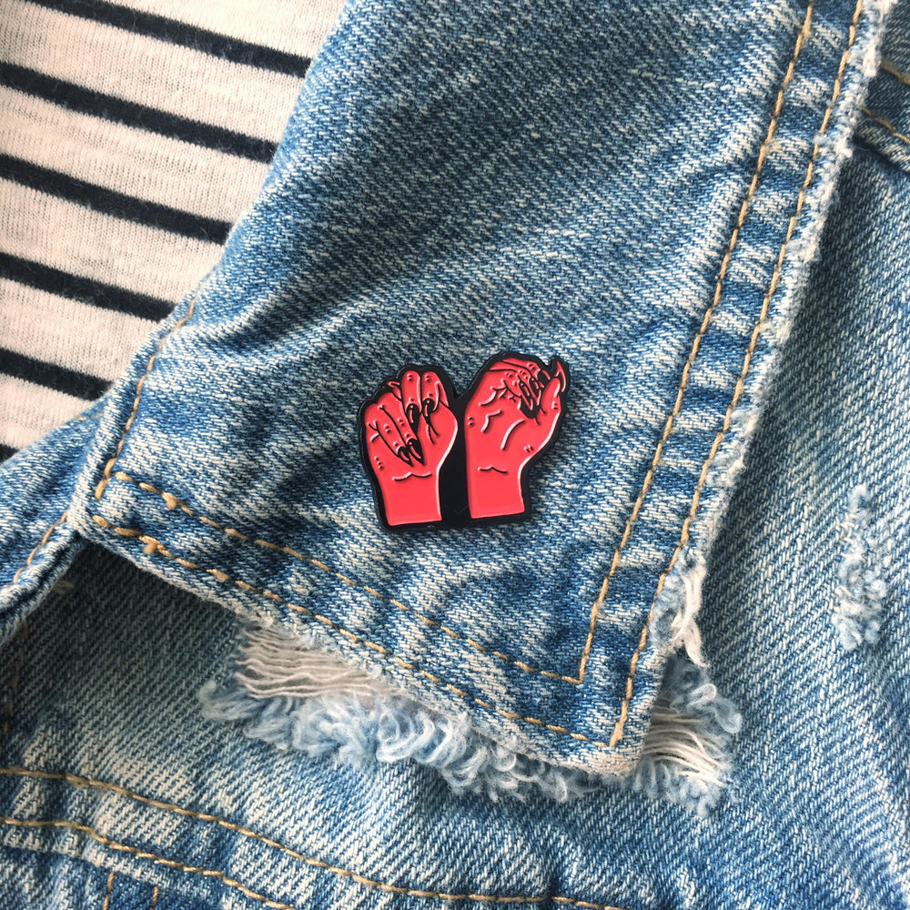 "A feminist enamel pin of the word ""No"" in American Sign Language. Worn on a denim jacket."