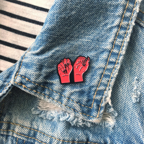 A cool enamel pin for hard of hearing feminists.