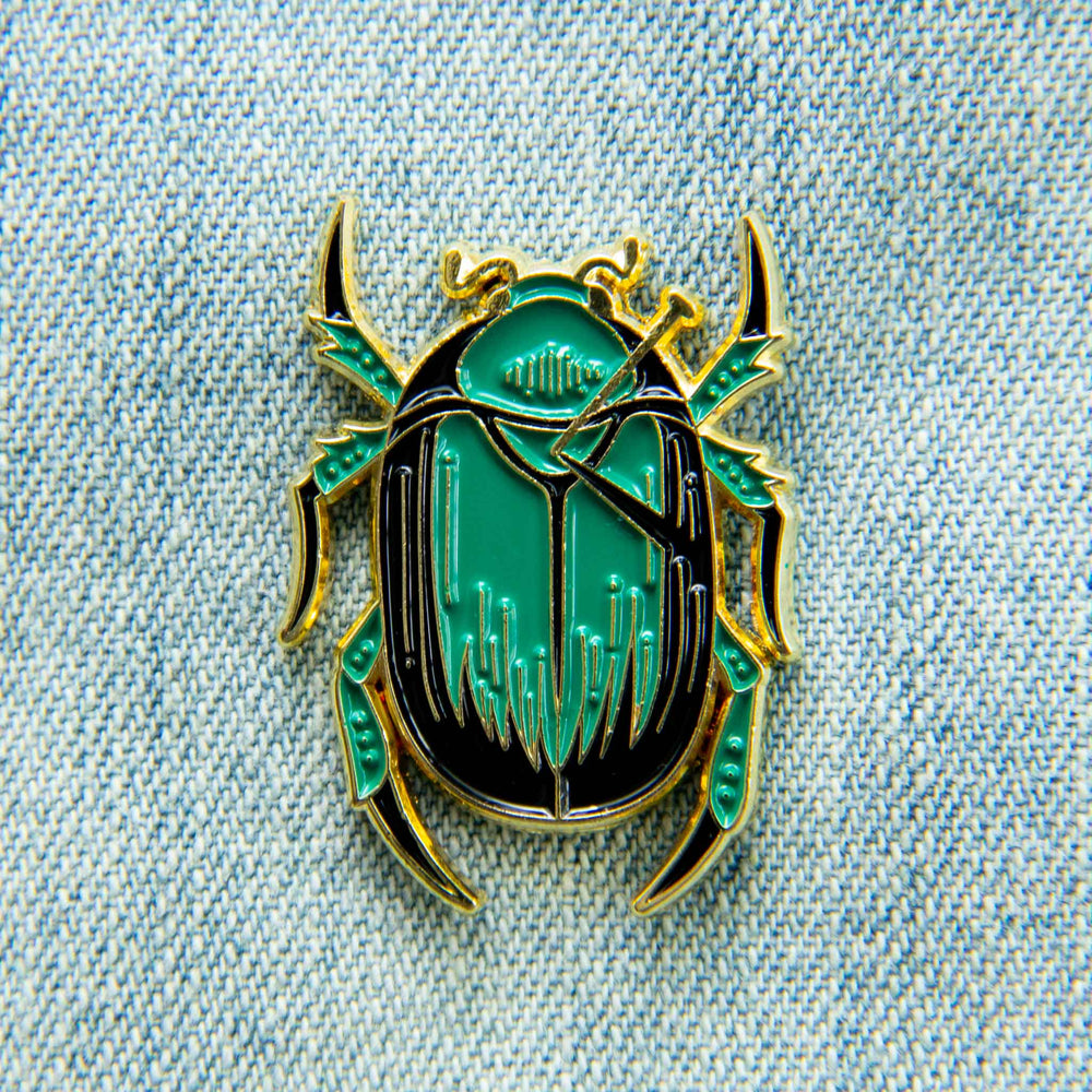 A curio themed enamel pin of a taxidermy green scarab beetle, plated in gold metal.