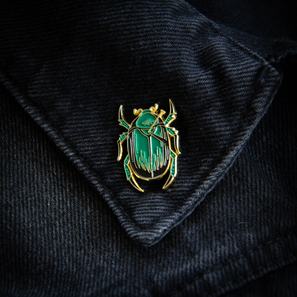 A witchy scarab insect enamel pin on the lapel of a women's black denim jacket.