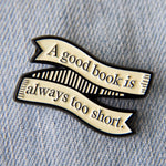 "A literary enamel pin of a banner with the Jane Austen quote, ""A Good Book is Always too Short""."
