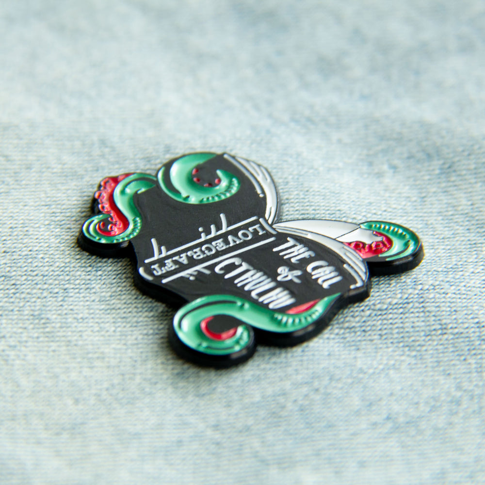 "An enamel pin of Lovecraft's ""The Call of Cthulhu"" book, for nerdy horror fashion."