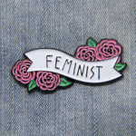 Feminist enamel pin with a quote on a banner surrounded by pink flowers. Fashion for a women's march.