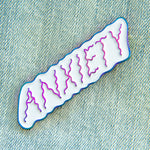 "A cute enamel pin of the word ""Anxiety"" in rainbow colors."