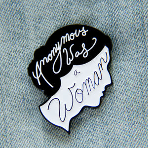 "A black and white enamel pin of Virginia Woolf's silhouette with her quote, ""anonymous was a woman""."
