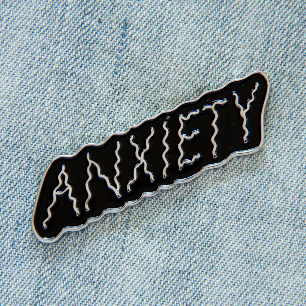 "Load image into Gallery viewer, A black and silver enamel pin of the word, ""anxiety"" for mental health awareness."
