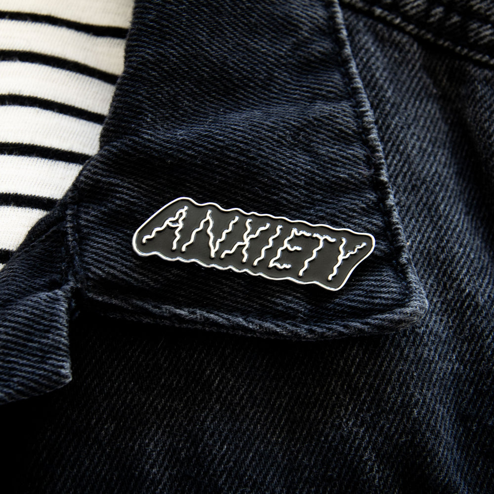 "A stylish lapel pin of the word ""Anxiety"" for men and women's fashion."