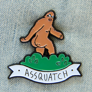 "A funny enamel pin of a sasquatch with a huge butt and the quote, ""assquatch""."