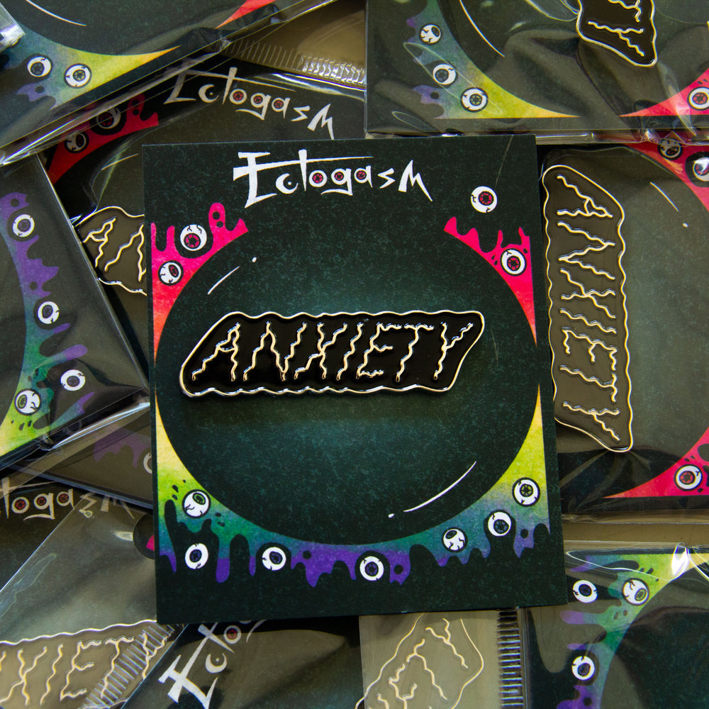 "A black and silver ""Anxiety"" enamel pin for unisex style."