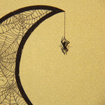 Wall decor of a black widow hanging from a moon made from cobwebs.