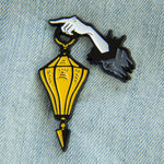 A spooky enamel pin of a ghostly hand holding a yellow lantern.