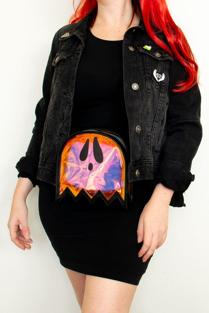 A punk rock outfit of a black bodycon dress, black denim jacket with pins and patches, and a ghost shaped holographic fanny pack.
