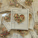 A heart shaped enamel pin for people who love to read and write.
