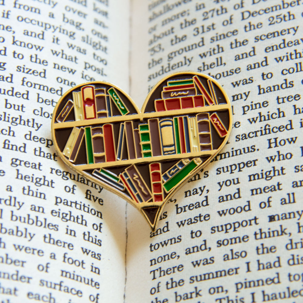 A literature themed enamel pin inside of a book.